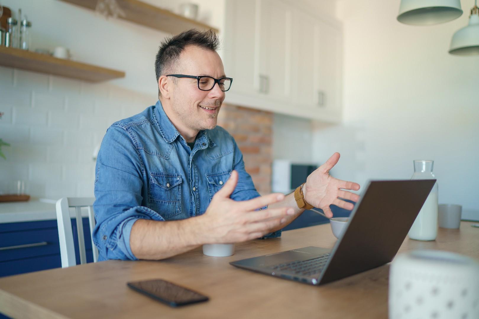 Mann-sitzt-am-Laptop-im Homeoffice-und-argumentiert-im-Call