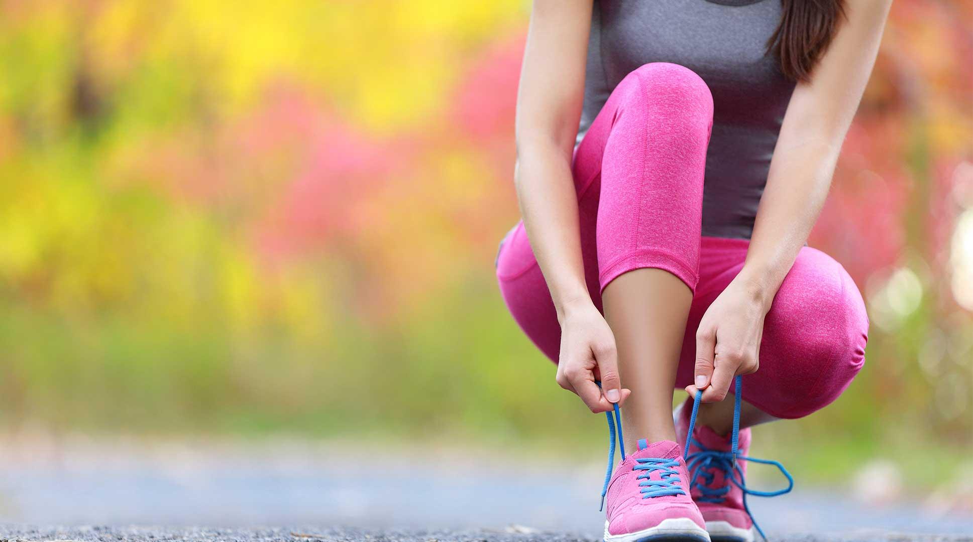 junge-frau-im-sportoutfit-bindet-schuhe-für-schrittwettbewerb